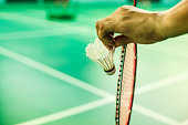Closeup Badminton player hand holding the shuttle cock together with the racket, ready to serve position on the play green court with copy space
