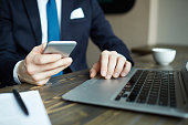 Closeup portrait of elegant businessman working with laptop and holding smartphone while networking at workplace