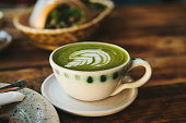 Close-up - ceramic cup with green tea with milky foam with beautiful pattern on the background of blurry basket with food