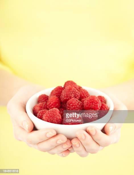 Gros plan de récolte de femme tenant un bol avec des framboises