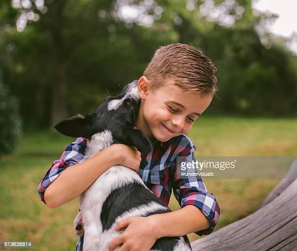 Rascal primer plano de lindo niño da su cachorro una gran abrazo