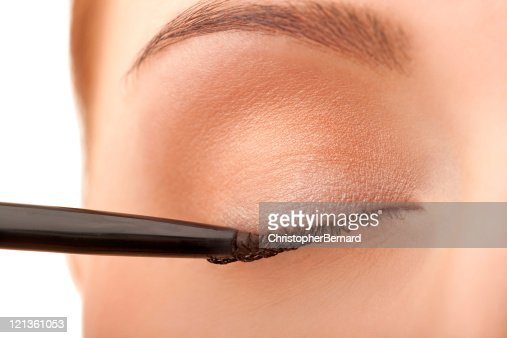 Close-up female applying eye liner