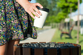 Close-up female hand throwing paper cup on trash bin outside in park with copy text space area