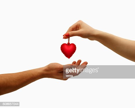 closeup girl's hand giving red heart in hand men : Stock Photo