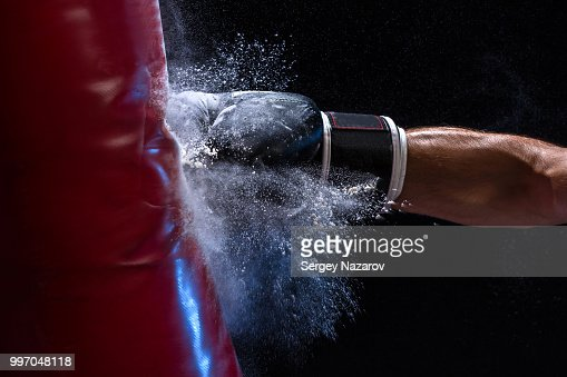 Close-up hand of boxer at the moment of impact on punching bag over black background : Stock Photo