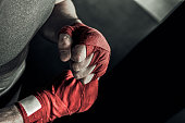 Closeup male hand of boxer with red boxing bandages. Fists of fighter before the fight or training in sport gym.