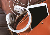 closeup headphones and tablet computer in bag on wooden table with soft-focus in the background. film colors tone