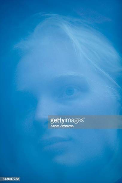 Closeup headshot of a blonde woman behind a window bus reflecting the blue sky front view on August 28 2006 in Russia