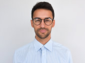 Closeup headshot of handsome attractive male, looks directly at the camera, wears round spectacles, isolated over white background. Portrait of smart bristle student wearing casual blue shirt. People