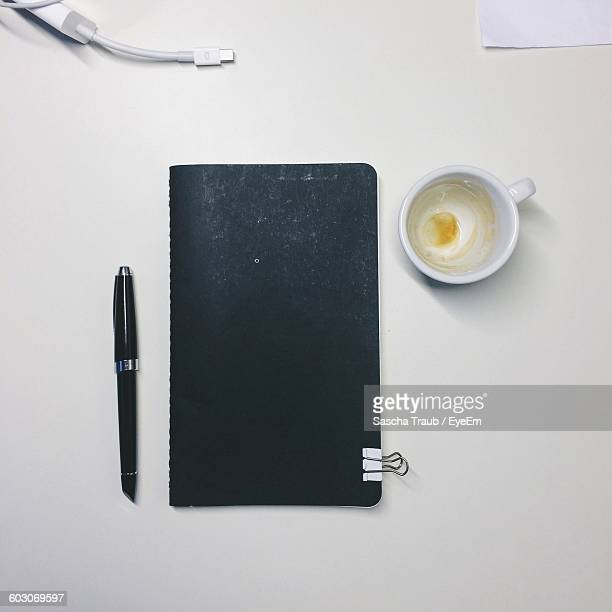 Close-Up High Angle View Of Coffee Cup And Diary On Table