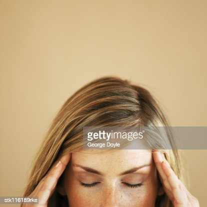 Close-up high section of a young woman touching her head with eyes closed