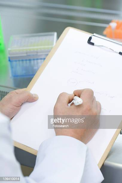Close-up human hands writing a document in laboratory, high angel view, Differential Focus