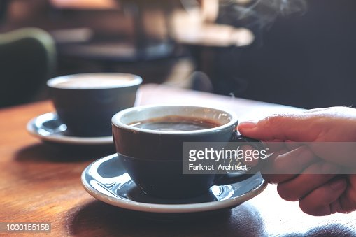 Closeup image of a hand holding a blue cup of hot coffee with smoke on wooden table in cafe : Stock Photo