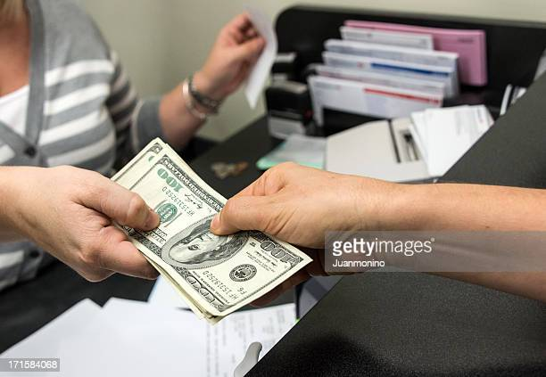 close-up image of a woman getting a cash from a bank teller