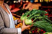 Close-up image of a woman holding kohlrabi at market.
