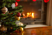 Closeup image of golden and red baubles on Christmas tree in front of burning fireplace. Beautiful Christmas background