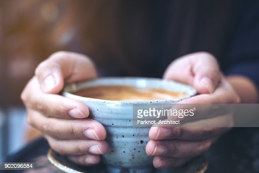 Closeup image of hands holding a cup of hot coffee on glass table in cafe : Stock Photo