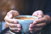 Closeup image of hands holding a cup of hot coffee on glass table in cafe