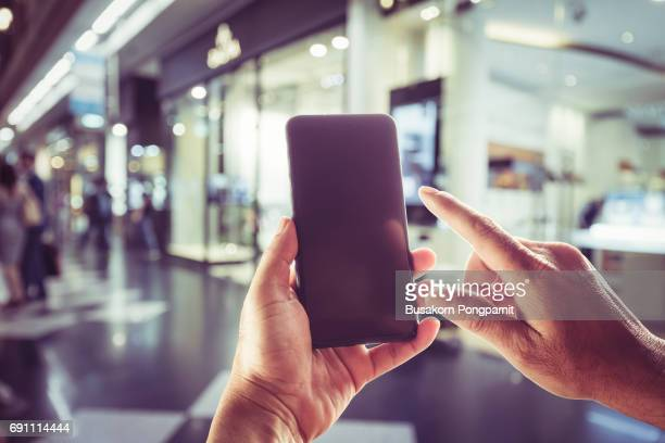Close-up image of male hands using smartphone. Blurred background on city shopping,  searching or social networks concept