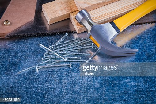 Close-up image of metal nails hammer wooden bricks hacksaw : Bildbanksbilder