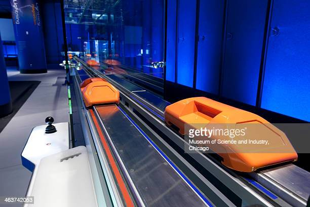 Closeup image of orange cars on a track with embedded electromagnets that are part of the magnetic levitation display in the Science Storms exhibit...