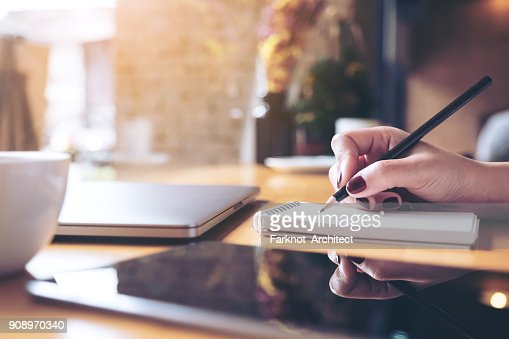 Closeup image of woman's hand writing on a blank notebook with laptop , tablet and coffee cup on wooden table background : Stock Photo