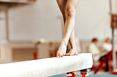 closeup legs women gymnasts exercises on balance beam
