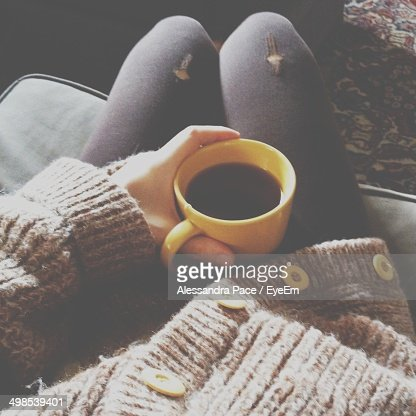 Close-up mid section of hand holding coffee cup on lap