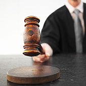 Close-up mid section of male judge banging gavel