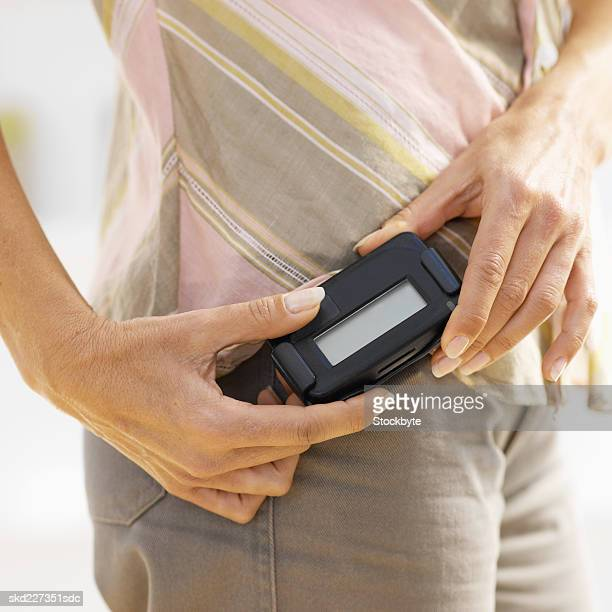 Close-up mid section of woman touching pager