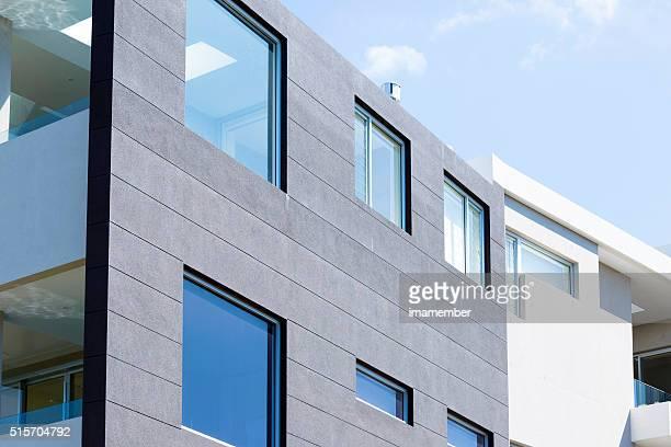 Closeup modern apartment building against blue sky, copy space