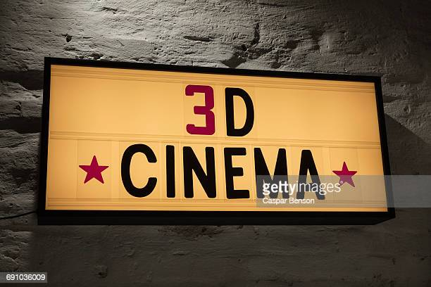 Close-up of 3D Cinema signboard against gray wall