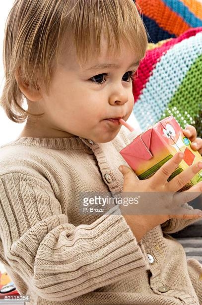 Close-up of a baby boy drinking juice from a carton with a drinking straw