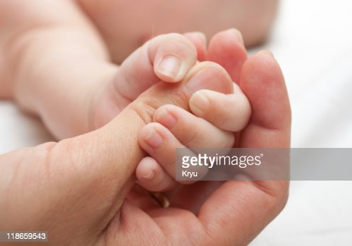 Close-up of a baby holding the thumb of an adult : Stock Photo