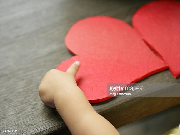Close-up of a baby's hand with two valentine hearts