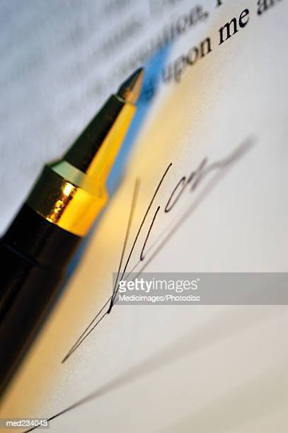 Close-up of a ball point pen with a signature on paper