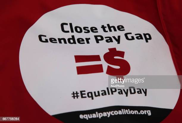 Closeup of a banner as women rally to demand equal pay for women and an end to the wage gap between the sexes on 'Equal Pay Day' in Toronto Ontario...