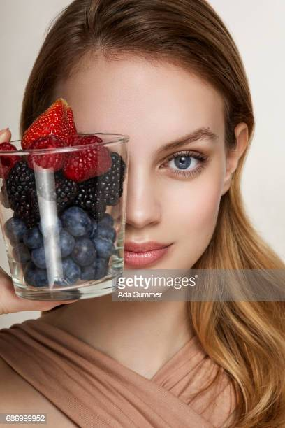 close-up of a beautifu young woman holding a glass full of red berries