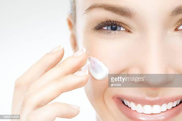 Close-up di una bella donna applicando crema per il viso