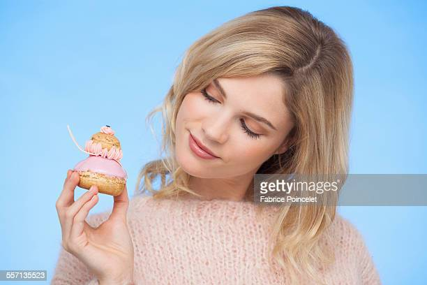 Close-up of a beautiful woman holding a french strawberry religieuse