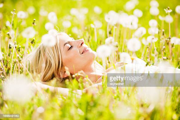 Close-up of a beautiful young woman among dandelions.