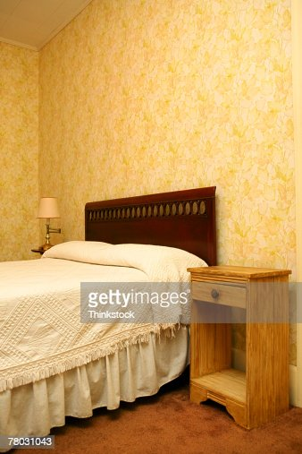 Close-up of a bed with a bedside table. : Stock Photo