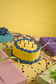 Close-up of a birthday cake and birthday presents on a table