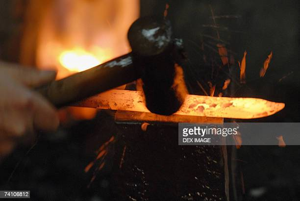 Close-up of a blacksmith's hand hitting a heated metal rod with a hammer