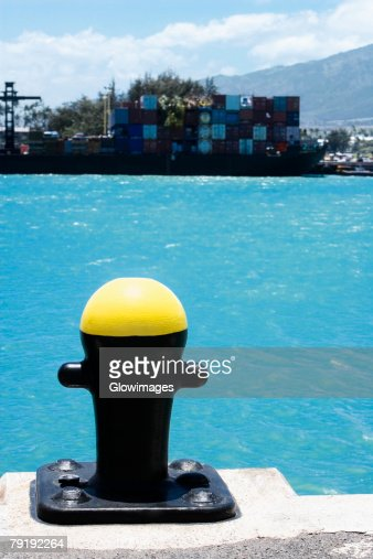 Close-up of a bollard with cargo containers in the background at a commercial dock : Stock Photo