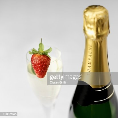 Close-up of a bottle of champagne with a glass of champagne and a strawberry in the background : Stock Photo