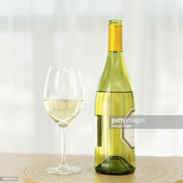 close-up of a bottle of white wine with a wineglass on a table