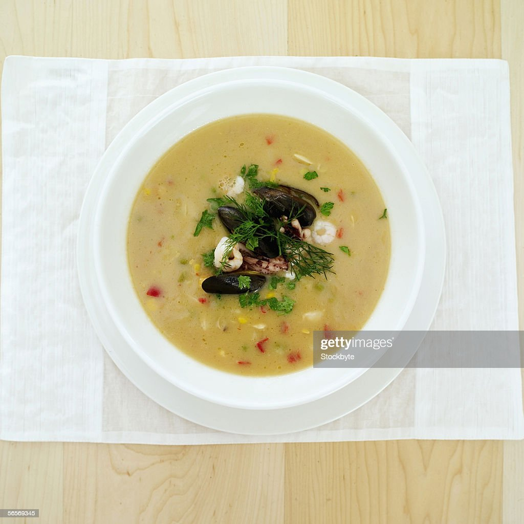 close-up of a bowl of soup garnished with seafood : Stock Photo