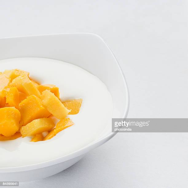 Close-up of a bowl with mango slices and cream