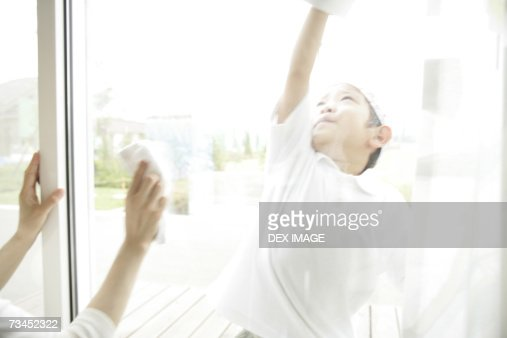 Close-up of a boy cleaning a window : Stock Photo